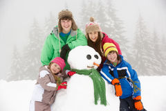 Grupo de niños que construyen el muñeco de nieve el día de fiesta del esquí Imagenes de archivo