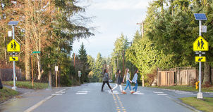 Grupo de niños que cruzan con seguridad la calle de la escuela Foto de archivo libre de regalías