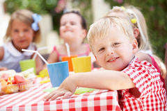 Grupo de niños que disfrutan del partido de té al aire libre Imagenes de archivo
