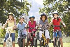 Grupo de niños que montan las bicis en campo Imagen de archivo libre de regalías