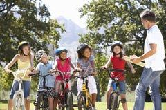 Grupo de niños que tienen lección de la seguridad del adulto mientras que monta Bikes en campo Fotos de archivo