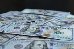 Grupo de 100 notas de dólar no fundo preto Imagens de Stock