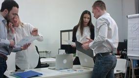 Grupo de oficinistas con los diagramas que se preparan para la presentación del negocio metrajes