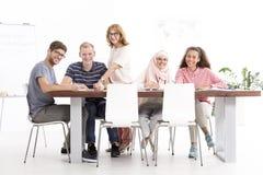 Grupo de oyentes que se sientan en la tabla durante el curso de idiomas fotos de archivo