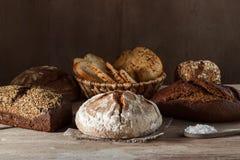 Grupo de pão do trigo e de centeio com uma colher do sal em um fundo de madeira Fotografia de Stock Royalty Free