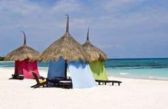 Grupo de palapas coloridos en una playa tropical imagenes de archivo