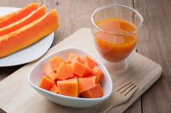 Grupo de papaya anaranjada en el plato blanco, el jugo de papaya y los vagos de madera imágenes de archivo libres de regalías