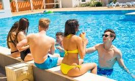 Grupo de pares alegres que bebe cocktailsin la piscina Imagen de archivo