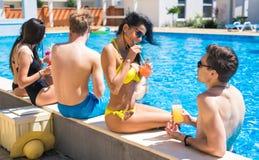 Grupo de pares alegres que bebe los cócteles en la piscina Imágenes de archivo libres de regalías