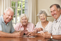Grupo de pares superiores que aprecia o jogo dos cartões em casa fotografia de stock