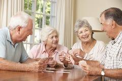 Grupo de pares superiores que aprecia o jogo dos cartões em casa imagem de stock royalty free