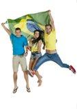 Grupo de partidarios felices jovenes del deporte con la bandera del Brasil Imagen de archivo