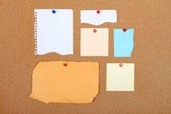 Grupo de pedazos de papel vacíos en tablón de anuncios. Fotografía de archivo
