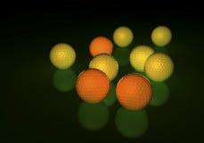 Grupo de pelotas de golf amarillas y anaranjadas, brillando intensamente en una superficie reflectora Imágenes de archivo libres de regalías