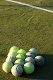 Grupo de pelotas de tenis delante de la línea blanca en corte Imagen de archivo