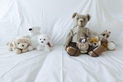 Grupo de peluches lindos en un sofá blanco Foto de archivo