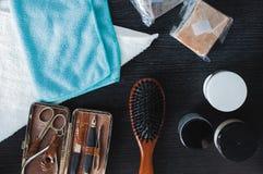 Grupo de pente de madeira, de jogo do tratamento de mãos, de gel de cabelo e de toalhas coloridas no fundo escuro Foto de Stock