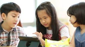 Grupo de pequeño niño asiático que come el bocado y que juega así como una tableta del ordenador almacen de video