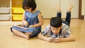 Grupo de pequeño niño asiático que come el bocado y que juega así como una tableta del ordenador almacen de metraje de vídeo
