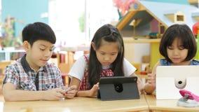 Grupo de pequeño niño asiático que juega así como una tableta del ordenador almacen de video
