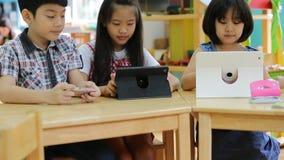 Grupo de pequeño niño asiático que juega así como una tableta del ordenador almacen de metraje de vídeo
