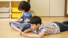 Grupo de pequeño niño asiático que juega así como una tableta del ordenador metrajes