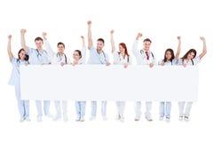 Grupo de personales de atención sanitaria que sostienen una bandera