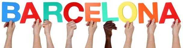 Grupo de personas étnico multi que lleva a cabo la palabra Barcelona imagen de archivo