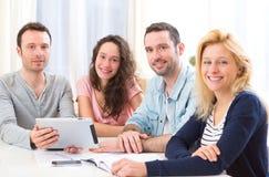 Grupo de 4 personas atractivas jovenes que trabajan en un ordenador portátil Foto de archivo libre de regalías