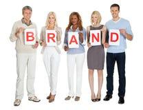 Grupo de personas casual con un tablero de la muestra de la marca Fotos de archivo libres de regalías