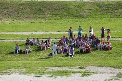 Grupo de personas con el casquillo rojo en el circo Maximus en Roma El esperar a comenzar Fotos de archivo