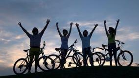 Grupo de personas con las bicicletas en el cielo de la puesta del sol almacen de metraje de vídeo