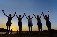 Grupo de personas con los brazos aumentados hechos excursionismo por el sol Fotos de archivo