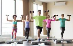 Grupo de personas con pesas de gimnasia y steppers Fotos de archivo libres de regalías