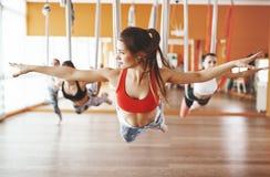 Grupo de personas contratado a una clase de yoga aero- en las hamacas antigravedad imagenes de archivo