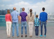 Grupo de personas de la parte posterior sobre orilla del agua de la ciudad Imágenes de archivo libres de regalías