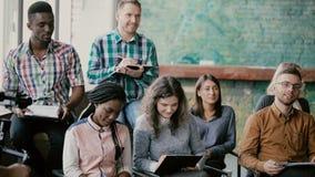 Grupo de personas de la raza mixta que se sienta junto y seminario del negocio que escucha Videograph del hombre con la película  metrajes