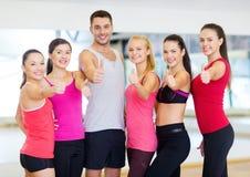 Grupo de personas en el gimnasio que muestra los pulgares para arriba Fotografía de archivo libre de regalías