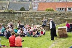 Grupo de personas en las ruinas de la abadía sobre la ciudad whitby 'editorial' Imagen de archivo libre de regalías