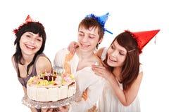 Grupo de personas en sombrero del partido con la torta. Foto de archivo libre de regalías