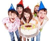Grupo de personas en sombrero del partido con la torta. Imagen de archivo libre de regalías