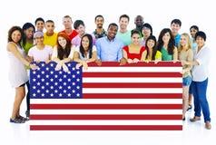 Grupo de personas grande que lleva a cabo el tablero de la bandera americana Foto de archivo