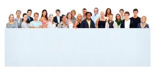 Grupo de personas grande que sostiene una cartelera vacía foto de archivo