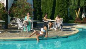 Grupo de personas joven que pasa tiempo en la piscina en un día de verano almacen de video