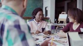 Grupo de personas de la raza mixta en la reunión de negocios en oficina moderna Líder de equipo de sexo femenino que da la direcc almacen de video