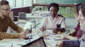 Grupo de personas de la raza mixta en la reunión de negocios en oficina moderna Líder de equipo de sexo femenino que da la direcc metrajes