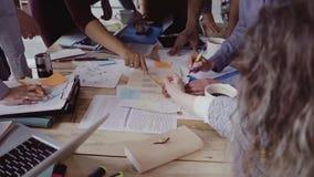 Grupo de personas de la raza mixta que se coloca cerca de la tabla Equipo joven del negocio que trabaja en proyecto de lanzamient almacen de video