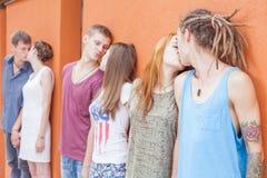 Grupo de personas medio que se besa y que se coloca cerca de fondo rojo de la pared Imágenes de archivo libres de regalías