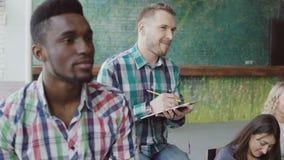 Grupo de personas multiétnico que se sienta en la oficina El hombre habla con la mujer, hace las notas Reunión de negocios en cow metrajes