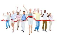 grupo de personas Multi-étnico que corre a la meta imagen de archivo